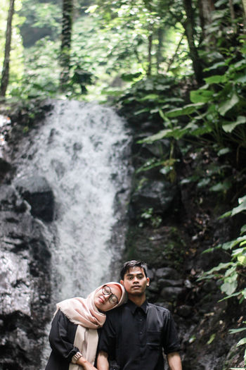 Couple standing against waterfall in forest