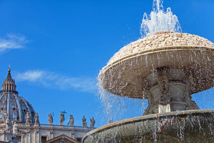 Low angle view of fountain against blue sky