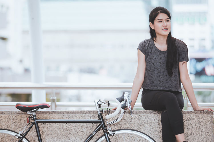 Portrait of beautiful woman with bicycle in city