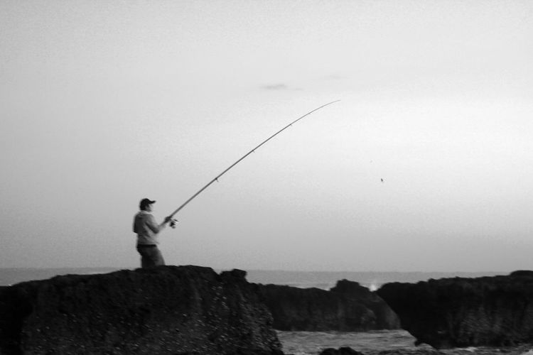 Fishing Rod Water Activity Leisure Activity Fishing Lifestyles Motion Outdoors Rock - Object Rock Nature Sea Sky Black And White