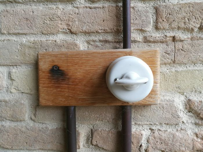 Close-up antique electric switch on brick wall