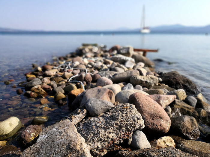 Stones near the sea Rock Beach Beauty In Nature Land Nature No People Outdoors Rock Rock - Object Sailboat Sea Sea And Sky Sky Stone Stone - Object Stone Material Water