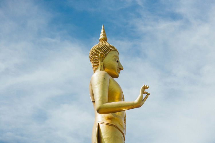 Low angle view of golden buddha statue against sky