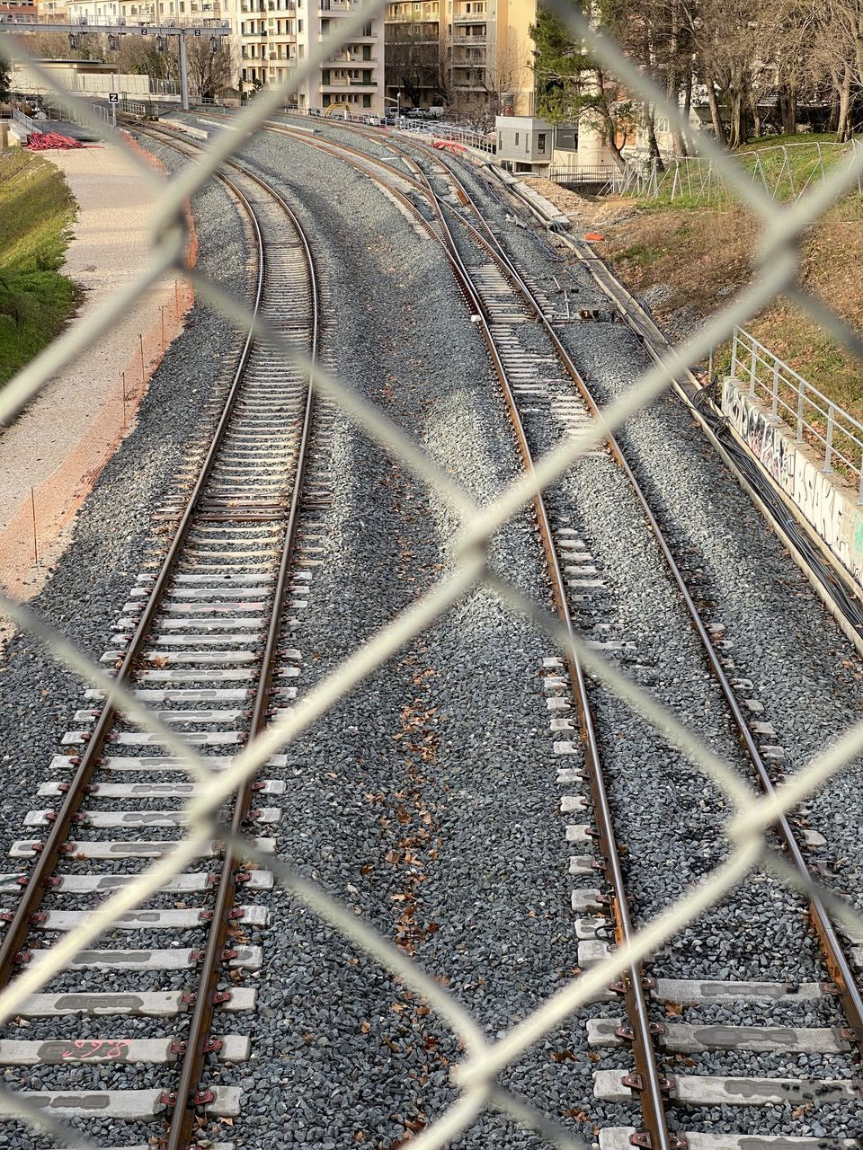 track, rail transportation, railroad track, transportation, fence, metal, no people, day, mode of transportation, high angle view, chainlink fence, the way forward, public transportation, direction, diminishing perspective, connection, nature, barrier, boundary, architecture, outdoors, long
