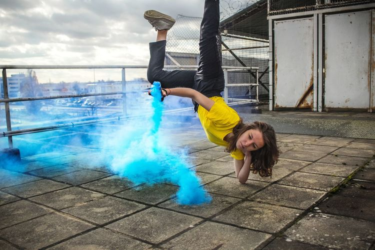 Young woman with smoke bomb doing breakdancing on roof