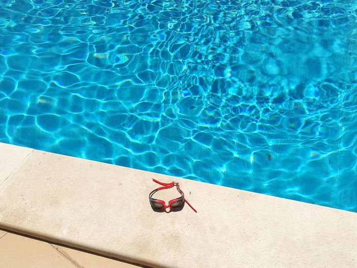 High Angle View Of Swimming Goggles On Poolside