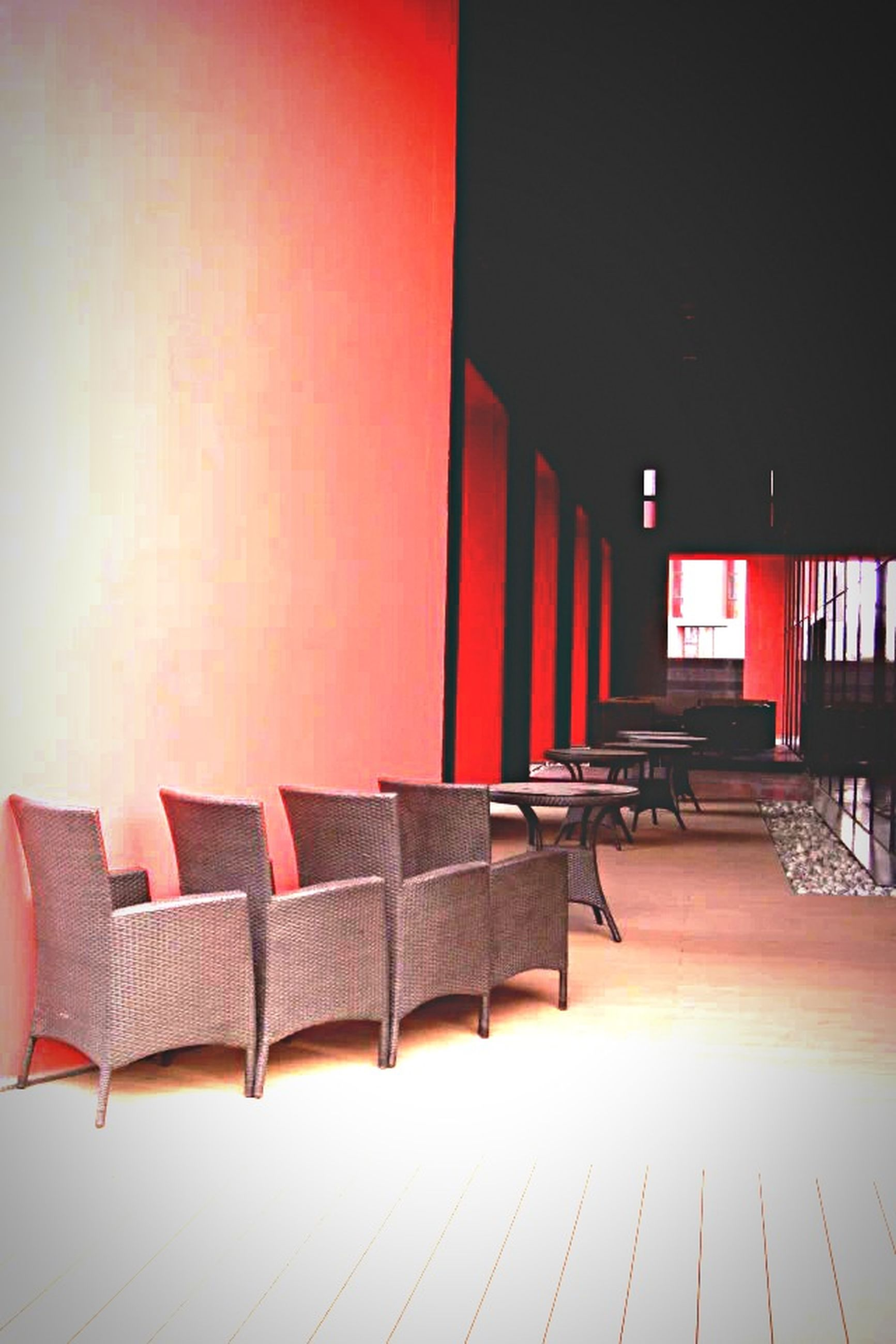 indoors, built structure, architecture, empty, chair, absence, in a row, wall - building feature, sunlight, no people, house, wall, flooring, shadow, furniture, seat, red, day, corridor, railing