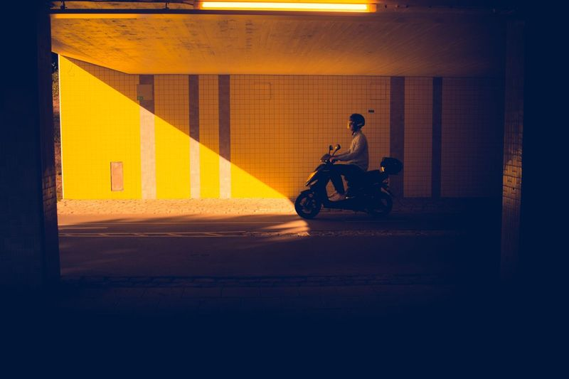 Man riding motorcycle on road at illuminated city