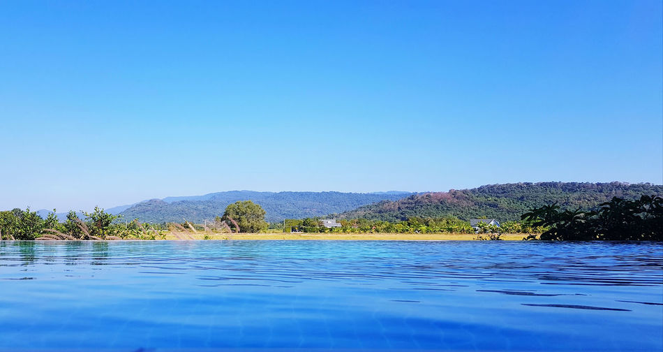 Scenic view of swimming pool by lake against clear blue sky