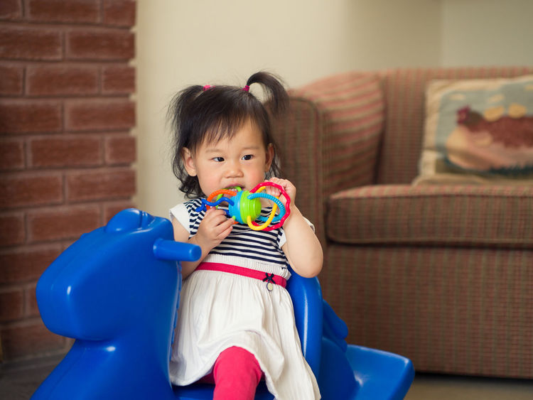 teething baby girl playing toy at home Teething Asian Baby Girl Baby Babyhood Childhood Cute Day Front View Full Length Holding Indoors  Innocence One Person People Playing Real People Rockinghorse Sitting Teething Baby Toy