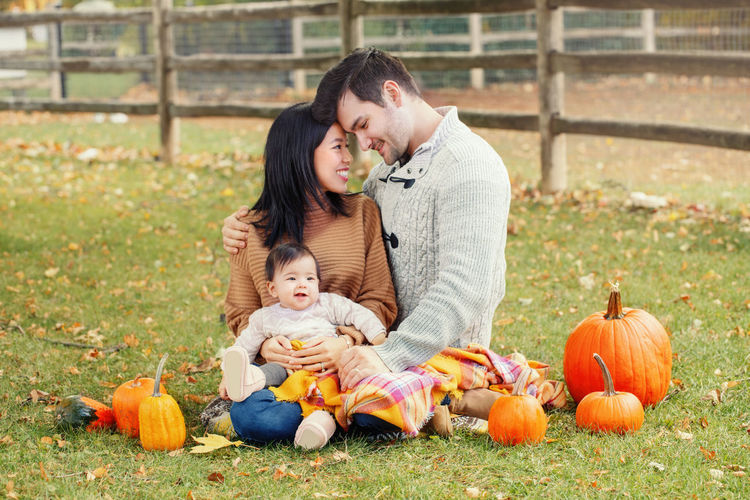 Family with pumpkins sitting on grassy land
