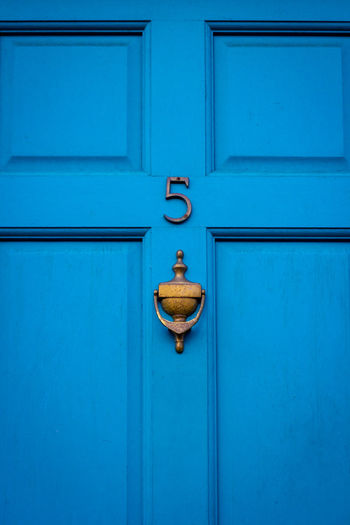 House number 5 on a blue wooden front door in london