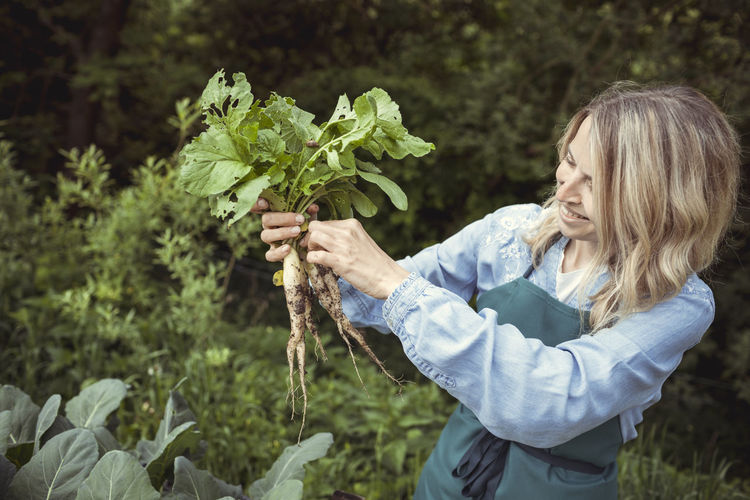Side view of woman holding plants