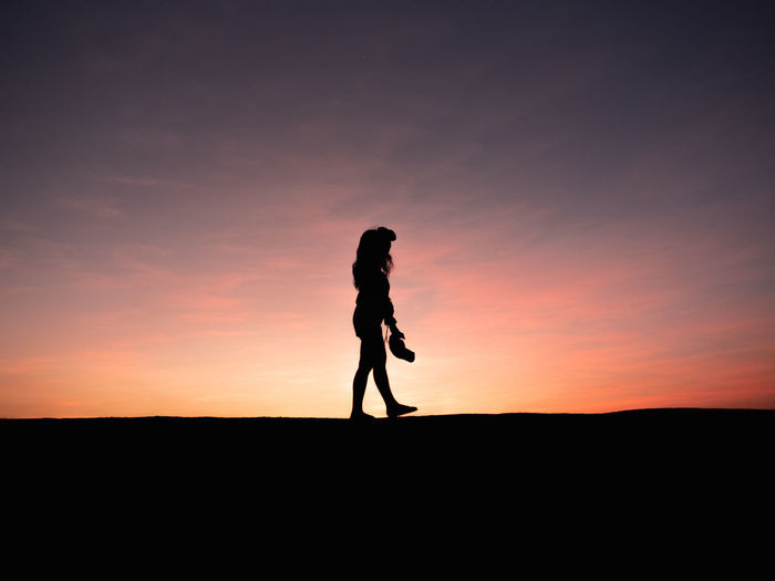 Silhouette woman walking on land against sky during sunset