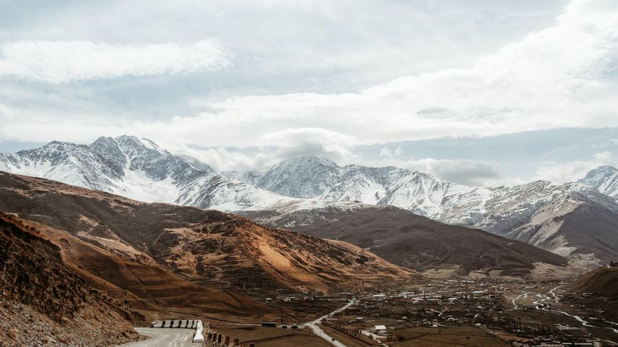 Snowcapped mountain range against cloudy sky