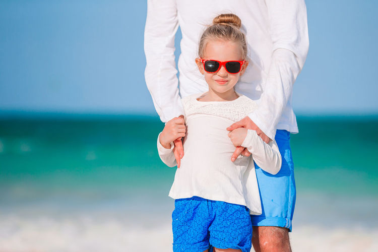 Portrait of woman wearing sunglasses at beach against sky