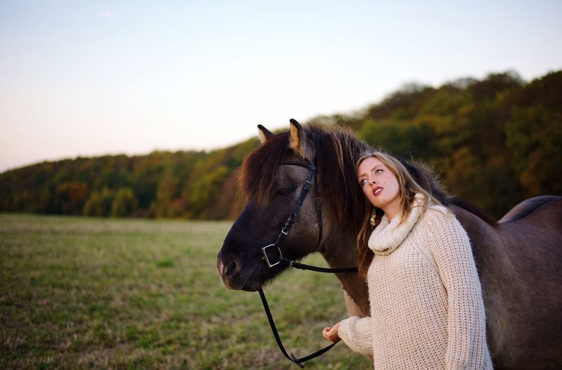 Beautiful young woman standing by horse on field during sunset