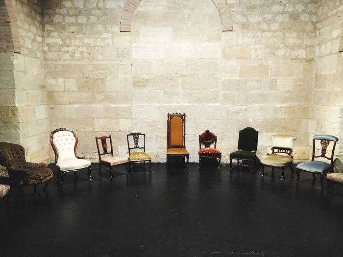 Empty chairs and tables against wall in building
