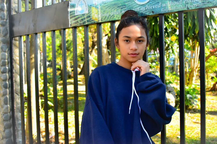 Portrait of teenage girl standing against gate