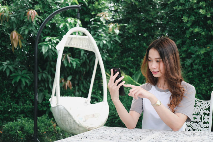 Young woman using smart phone sitting by plants outdoors
