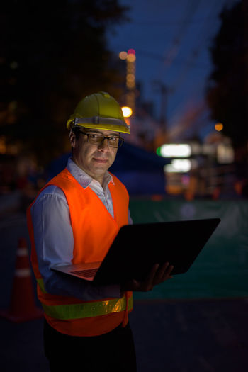 Man working on illuminated lighting equipment at night