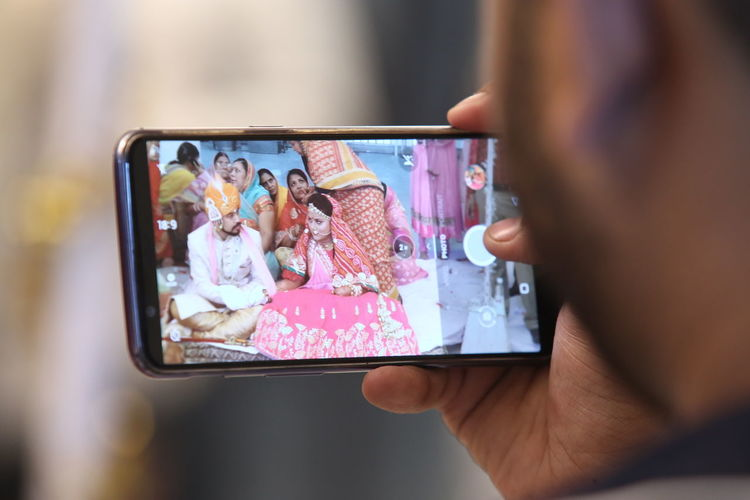 Cropped hand of young man photographing wedding with mobile phone
