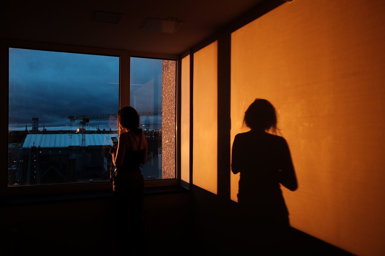 real people, standing, lifestyles, indoors, leisure activity, silhouette, window, one person, rear view, sky, women, men, architecture, nature, built structure, orange color, transparent, sunlight, looking at view
