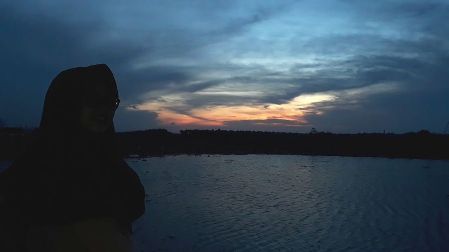 Silhouette man by sea against sky during sunset