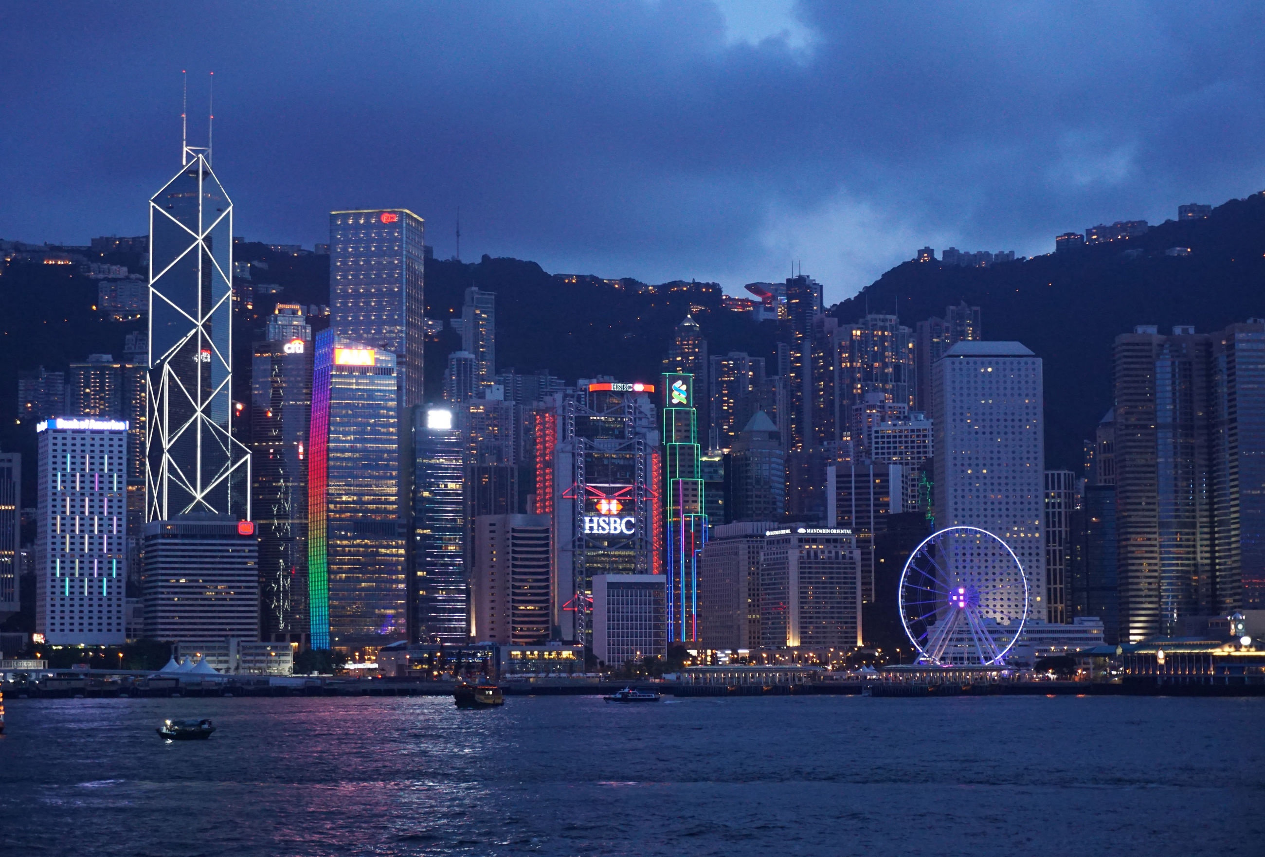 architecture, built structure, building exterior, city, illuminated, waterfront, skyscraper, water, development, modern, cityscape, night, dusk, travel destinations, urban skyline, building story, sky, tower, tall, city life, office building, tall - high, growth, outdoors, harbor, financial district, sea, in front of, skyline