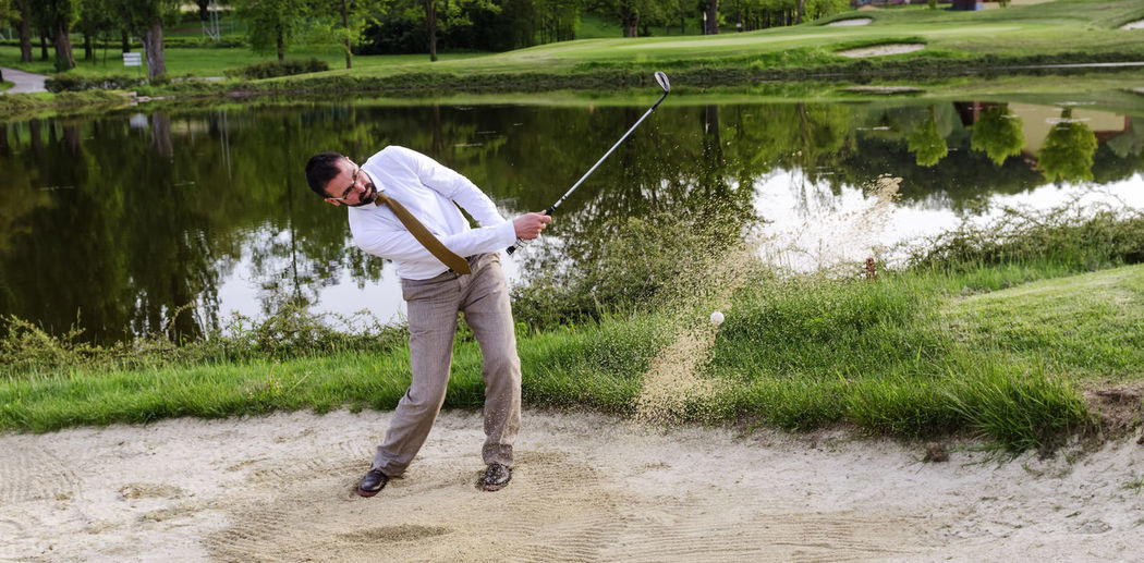 Businessman Golfer in Sand trap Businessman Casual Clothing Day Full Length Golf Golfswing Grass Grassy Green Color Growth Lake Leisure Activity Lifestyles Man Nature Outdoors Plant Play Sand Shooting Photos Tranquil Scene Tranquility Water