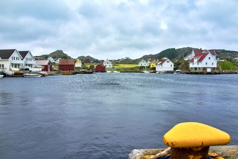 Norway, Utsira, Sørdvik: port Horizontal Day Outdoors Bollard Yellow Color Color Yellow Body Of Water Group Of Houses House Village Cloudy Overcast