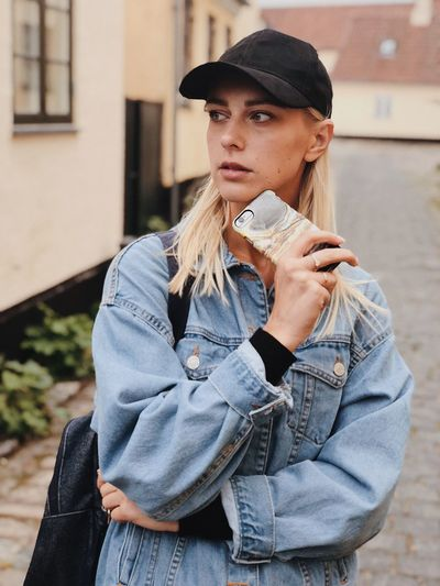 Mobile Phone One Person Lifestyles Real People Leisure Activity Young Adult Casual Clothing Architecture Front View Standing Day Looking Away Young Women Building Exterior Waist Up Clothing Built Structure Focus On Foreground Women Outdoors