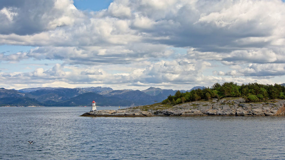 Rocck island with lighthouse in a Norwegian Fjord Cloudy Lysefjord Nature Norway Rock Island Fjord Island Landsape Lighthouse Mountain Mountains No People Norwegian Outdoors Sea Seascape Tranquility Water