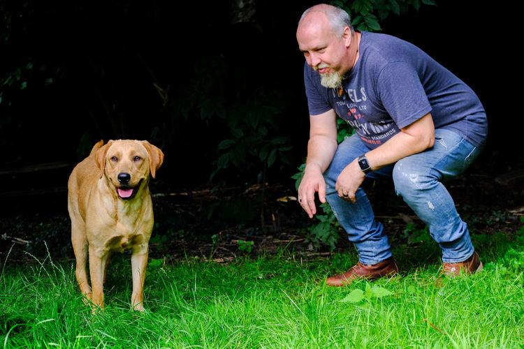 Full length of man and dog looking at farm