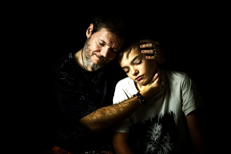 Close-Up Of Father And Son With Eyes Closed Against Black Background