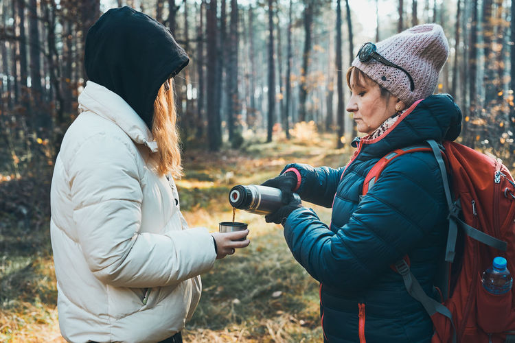 Mother and daughter with backpack having break during autumn trip pouring a hot drink from thermos