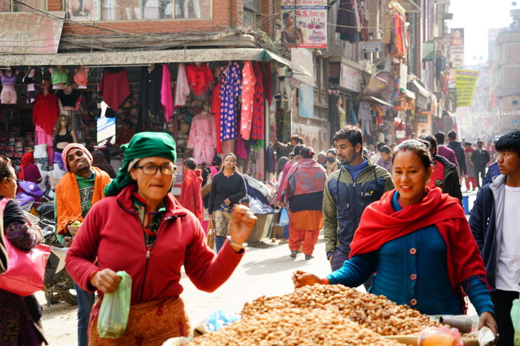 Group of people at market stall in city