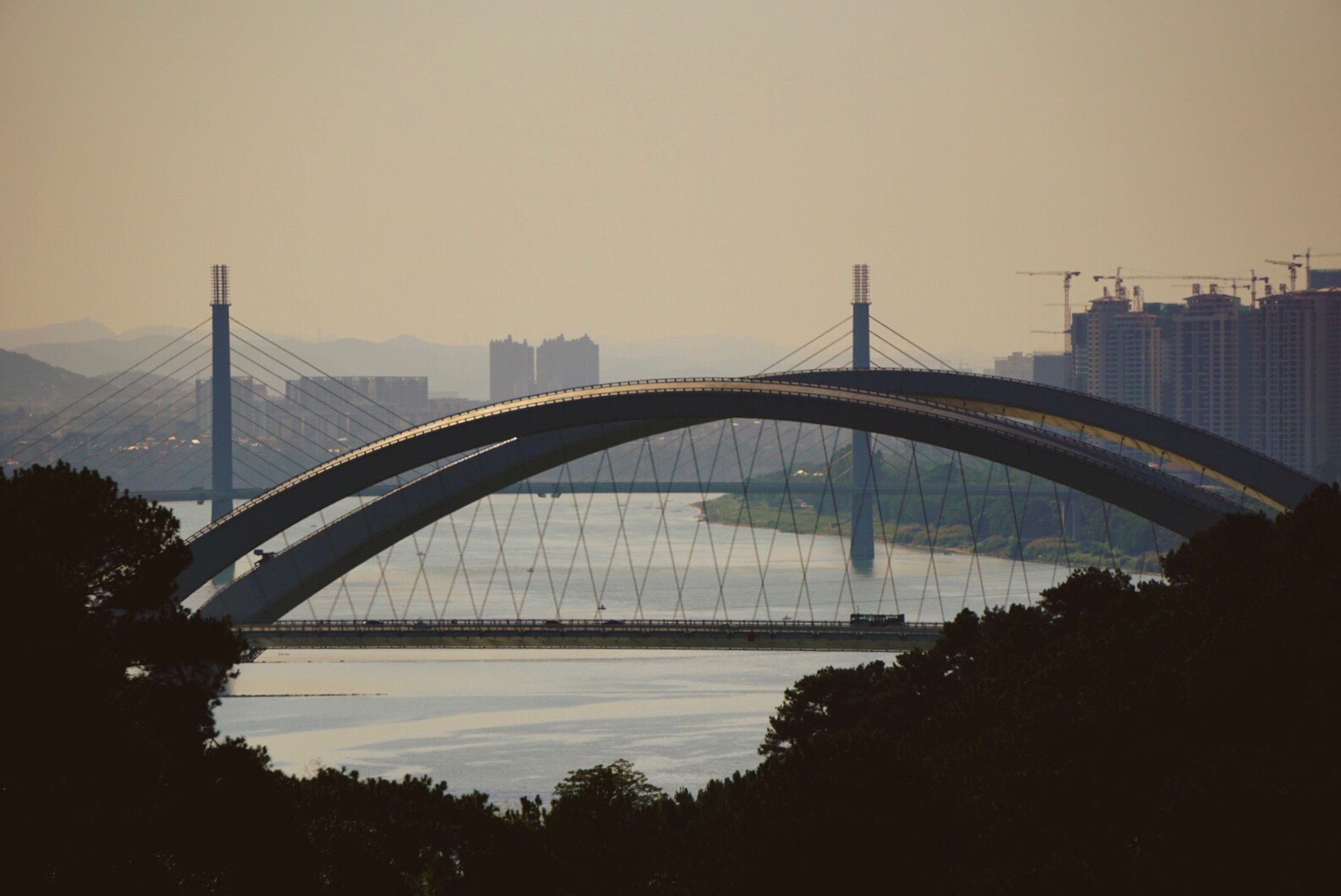 bridge - man made structure, sunset, connection, city, suspension bridge, travel destinations, transportation, outdoors, water, tourism, cityscape, architecture, sky, river, urban skyline, business finance and industry, no people, day