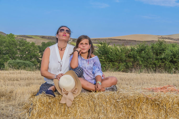 Portrait Of Mother And Daughter Sitting On Hay Bale Against Blue Sky