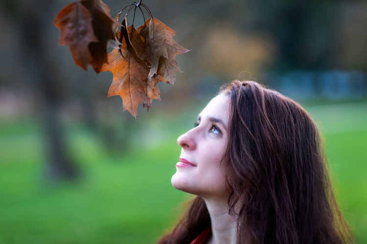 Close-up portrait of woman in autumn leaves