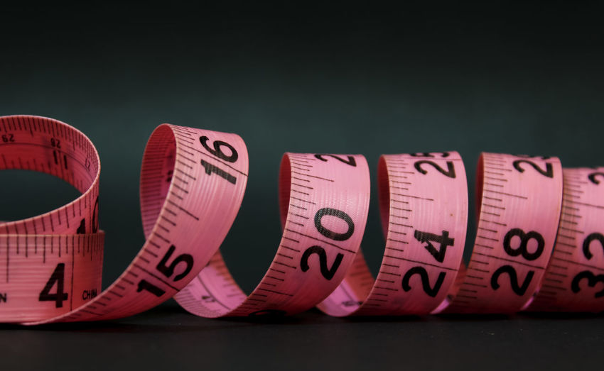 Close-up of tape measure over black background