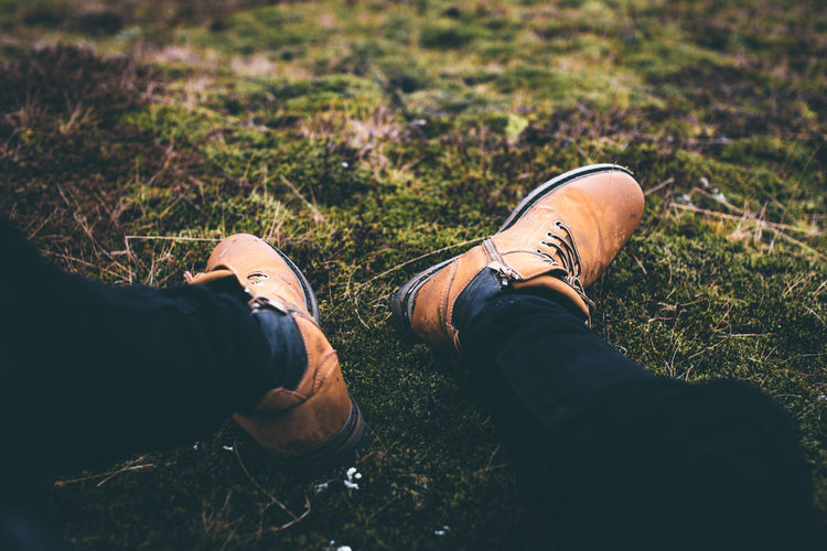 Low Section Shoe Human Leg Grass One Person Human Body Part Body Part Real People Personal Perspective Field Nature Leisure Activity Land Lifestyles Day High Angle View Men Outdoors Sitting Human Foot Jeans Human Limb