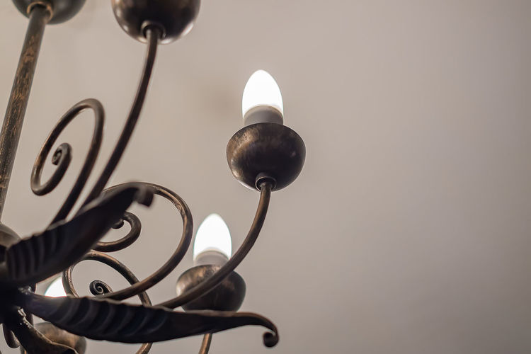 Low angle view of electric lamp against wall