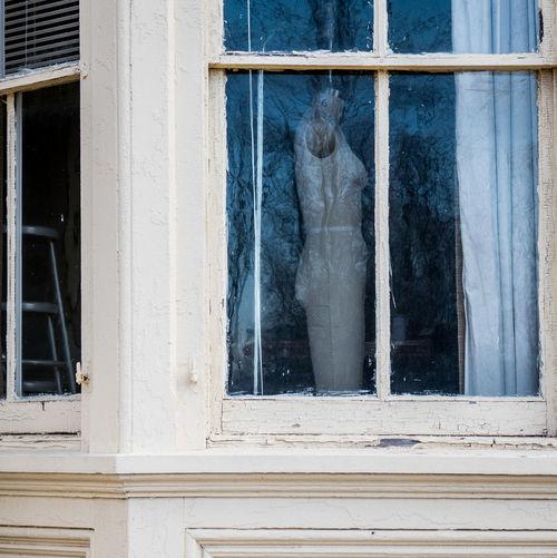 Dressmaker model seen through glass window