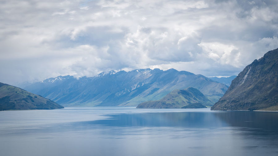 Scenic alpine lake surrounded by mountains shot on sunny day. location is lake hawea, new zealand