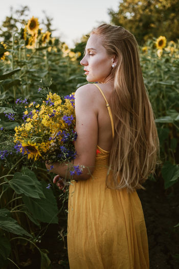 Young woman looking down while standing on yellow flowering plants