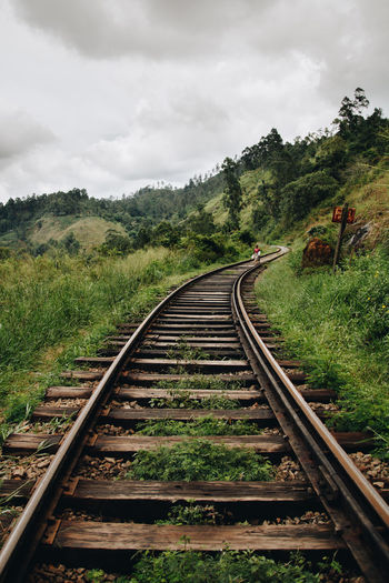 Railroad track on mountain against sky