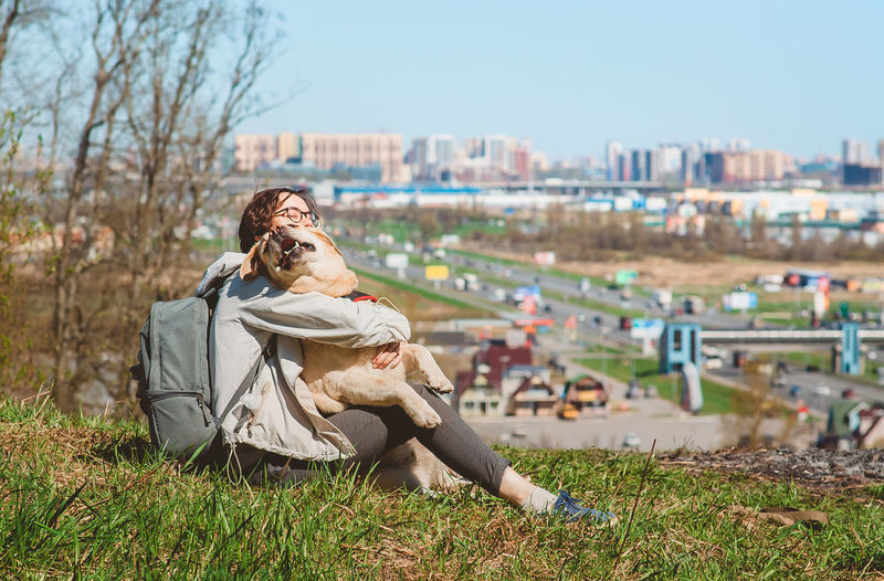 The girl hugs the labrador retriever and laughs, sitting on the mountain. vacation with a dog