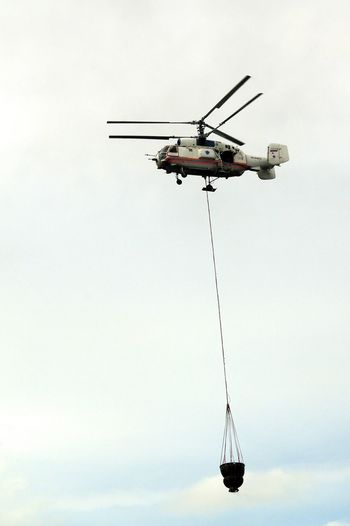The fire helicopter carries a water bucket to extinguish fire. Aerial Firefighting Bucket Clouds And Sky Day Fire Control Fire Suppression Flying Helicopter Helicopter Bucket Mode Of Transport No People Outdoors Sky Technology Transportation Water Water Bucket