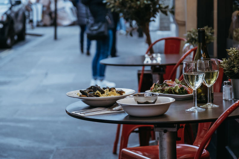 Plates with food and glasses of wine at the outdoor table of a restaurant, selective focus.